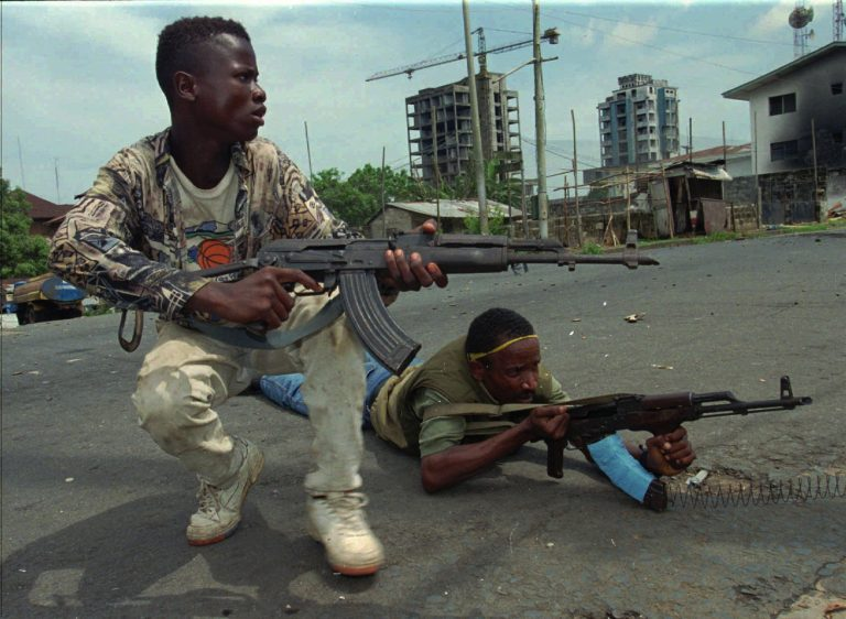 Fighters from the United Liberation Movement of Liberia (ULIMO) shoot their way through downtown Monrovia, LIberia Tuesday, April 16, 1996. (AP Photo/Jean-Marc Bouju)