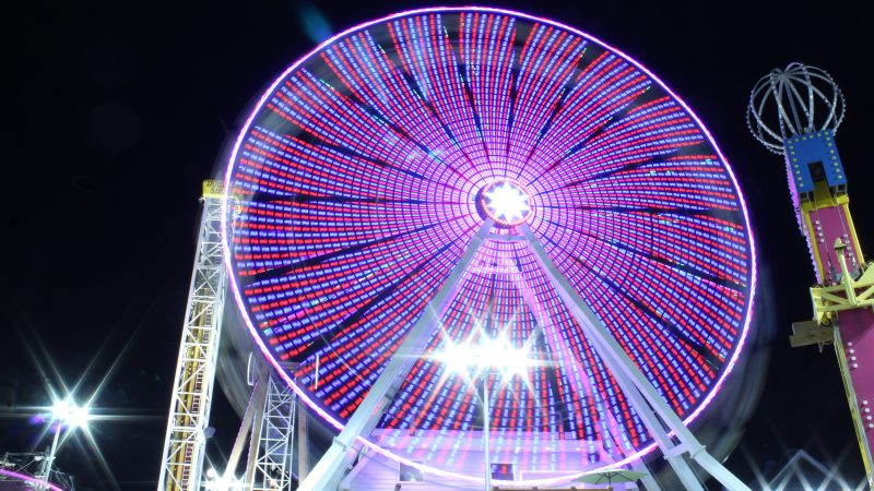 The lights of the Ferris wheel at Playland's Castaway Cove amusement park are a blur. Motorists coming over the Ninth Street Causeway can watch these and the lights of the Gillian's Wonderland Ferris wheel change and spin as they head into town. (Bill Barlow/for WHYY)