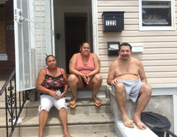 Ana Marrero, Milagros Soto, and Pablo Cuevas catching a cool breeze on the stoop of their home in Hunting Park. (Catalina Jaramillo/WHYY News)