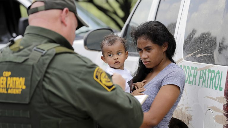 A mother migrating from Honduras holds her 1-year-old child as she surrenders to a U.S. Border Patrol agents after illegally crossing the border, near McAllen, Texas, in late June.