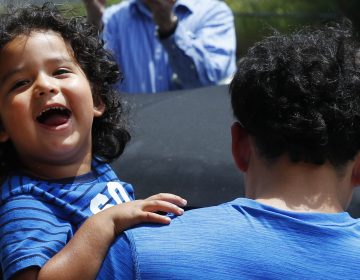 Ever Reyes Mejia, of Honduras, carries his son to a vehicle after being reunited and released by United States Immigration and Customs Enforcement in Grand Rapids, Mich. (Paul Sancya/AP)