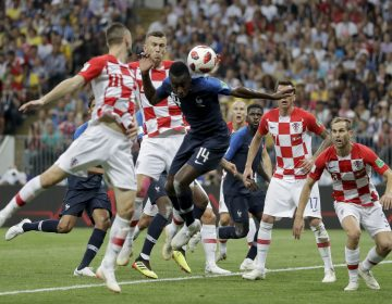 Croatia's Ivan Perisic, second left, handles the ball to give away a penalty as he jumps for the ball with France's Blaise Matuidi during the final match between France and Croatia. (Matthias Schrader/AP)