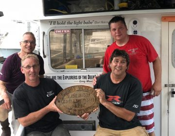 Dive Crew shows off the plate from boat sunk by German U-boats during World War II. Top Left Tom Packer, Bottom Left Rustin Cassway, Top Right, Mike Dudas, Bottom Right Brian Sullivan (Photo courtesy of Rustin Cassway)