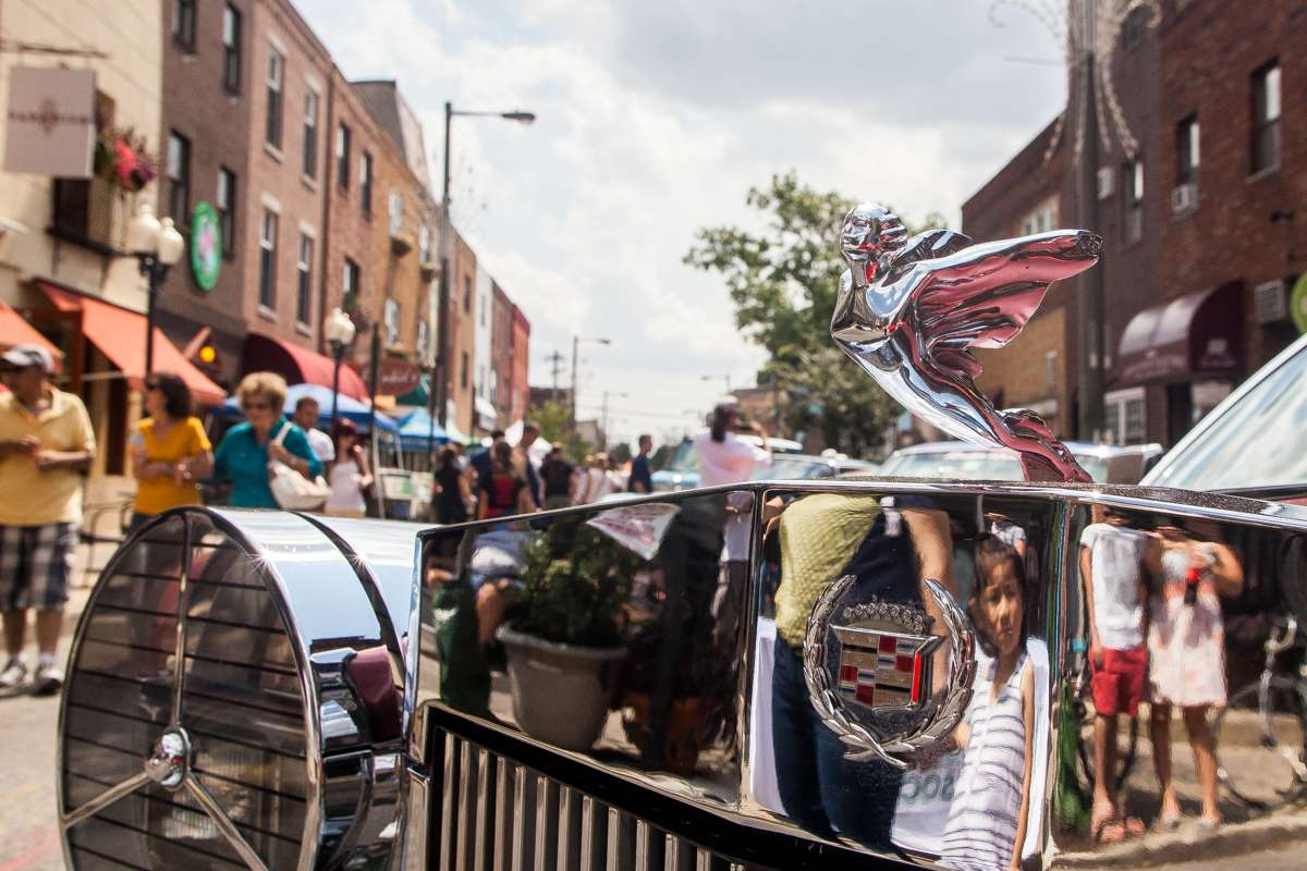 The chrome on a vintage Cadillac reflects the crowd at the Passyunk Avenue Car Show and Street Festival.
