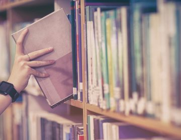 Student picking book from bookshelf at university (bigstockphoto.com)
