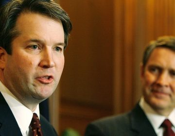 Brett Kavanaugh (left) speaks in 2006 when he was a nominee for the D.C. Circuit Court of Appeals. Then-Senate Majority Leader Bill Frist of Tennessee looks on. (Chip Somodevilla/Getty Images)