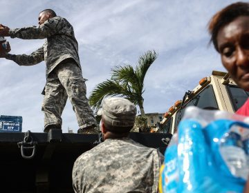 U.S. Army soldiers pass out water, provided by FEMA, to residents in a neighborhood without grid electricity or running water in San Isidro, Puerto Rico, on Oct. 17, 2017. (Mario Tama/Getty Images)