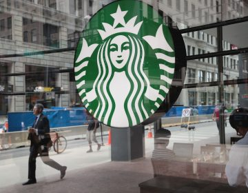 People walk by a Starbucks store in Chicago on May 29. Starbucks announced it plans on removing plastic straws from its 28,000 stores worldwide by 2020.