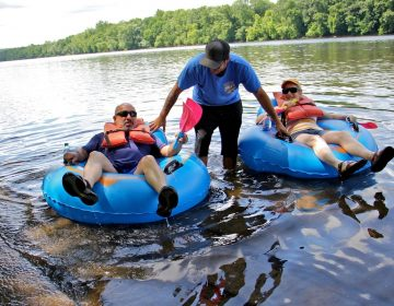 Matt Crance pushes off Marc and Robin Schaffer of Rockaway, New Jersey, at the Kingwood boat launch south of Frenchtown. (Emma Lee/WHYY)