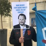 A protester holds up a sign targeting Salesforce CEO Marc Benioff outside the company's headquarters in San Francisco on Monday. (Laura Sydell/NPR)