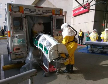 EMTs unload Parag S. Gohel from an ambulance at UPMC Presbyterian's ER. Gohel is in an isolation pod because he's pretending to have an infectious disease for the hospital's yearly drill. (Sarah Boden/WESA)
