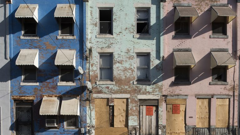 A row of houses, colorful but in need of substantial repairs, on North 27th Street in North Philadelphia.  (Jonathan Wilson for WHYY)