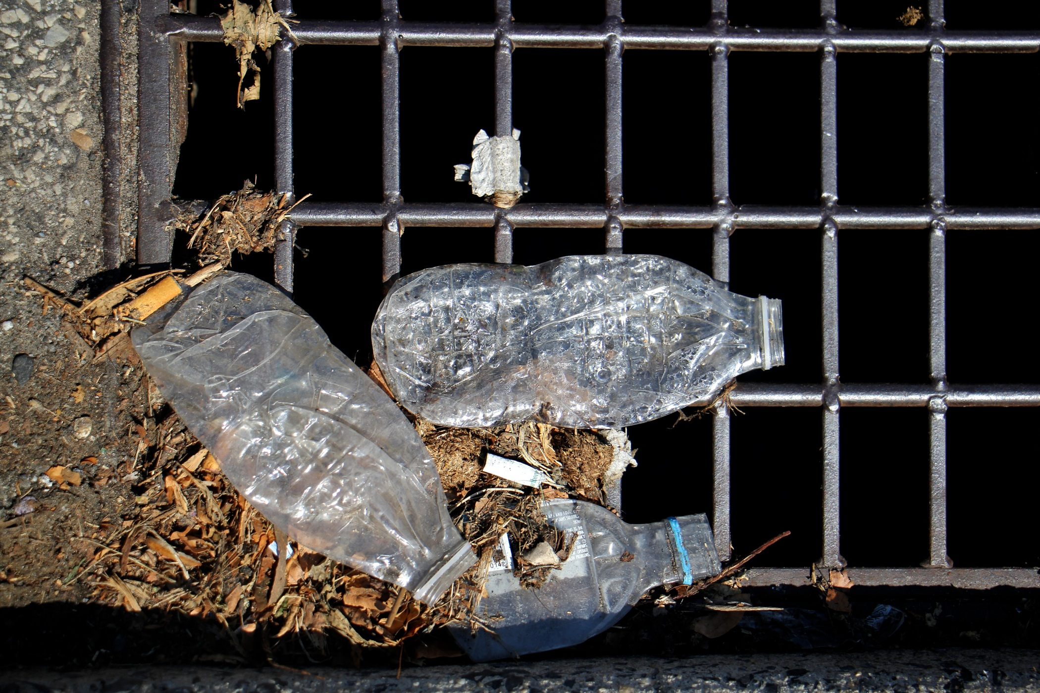 Plastic bottles accumulate on the grate of a storm drain.