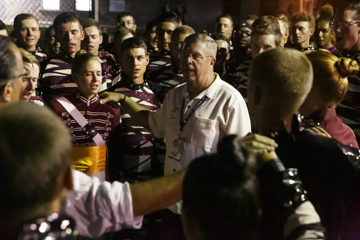 """Cadets Director Scott Litzenberg, center, leads the Cadets in the singing of their song, """"O Holy Name,""""before their first home performance of the summer. Litzenberg marched with the Cadets in 1982 and 1983."""