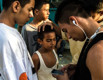 A group of older boys, some of whom are gang members, joke around with a younger boy. Neighborhood children are often groomed for gang activity from the age of 6 or 7. At first they may be given small assignments — like buying snacks for gang members or monitoring who's coming in and out of a neighborhood, says Ayuso. Bit by bit, he says, they graduate into bigger responsibilities. (Tomas Ayuso)