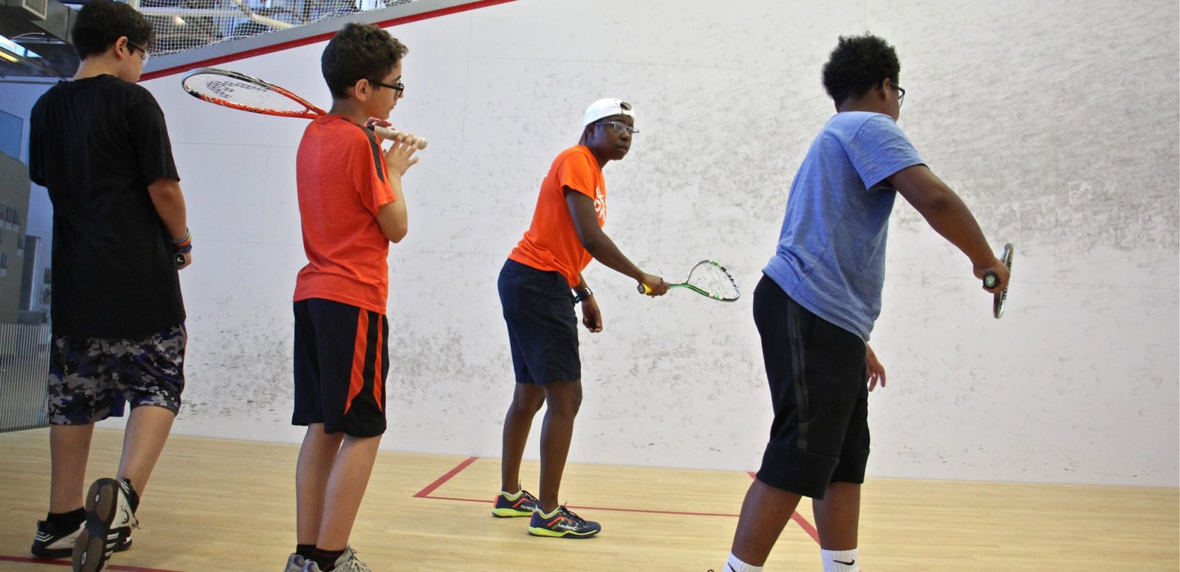 Squash coach Tempest Bowden runs drills with middle schoolers. (Emma Lee/WHYY)