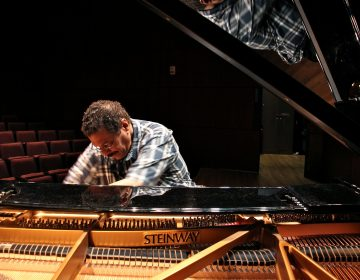 Composer and educator Alfonso Fuentes plays a black Steinway grand piano under a spotlight in a dark and empty auditorium at Princeton University