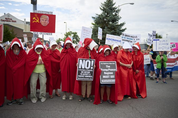 A group of 20 protesters dress as handmaids outside of the Make America Great Again rally in Wilkes-Barre, Pa., on August 2, 2018. (Natalie Piserchio for WHYY)