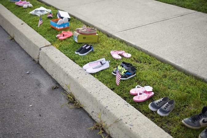 Children's shoes are seen lined up along the sidewalk during the Anti-Trump protest held outside of the Make America Great Again rally in Wilkes-Barre, Pa. on August 2, 2018. (Natalie Piserchio for WHYY)