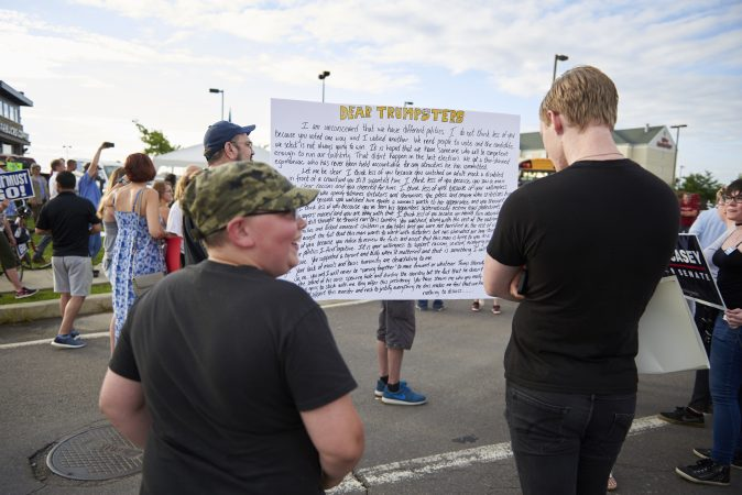 Trump supporters are seen reading an open letter from Trump Protesters at a demonstration outside of the Make America Great Again rally in Wilkes-Barre, Pa., on August 2, 2018. (Natalie Piserchio for WHYY)