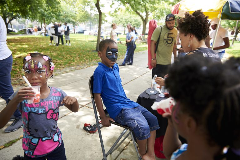 Quran, 6, of Southwest Philadelphia, has his face painted at the Southwark Projects Reunion at Jefferson Square Park by Latonia Brown, owner of Golden Brownie Art. (Natalie Piserchio for WHYY)