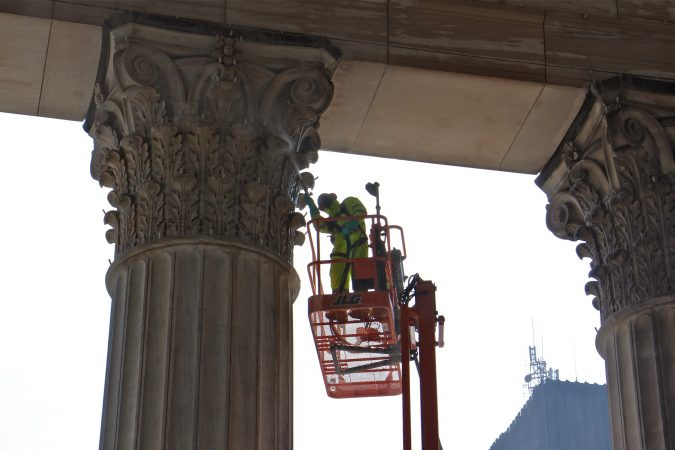 A worker cleans the ornate limestone capitals of the East Portico at 30th Street Station. (Emma Lee/WHYY)