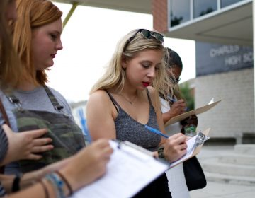 Young people register to vote outside a March for Our Lives gun control town hall at Universal Audenreid High School, in Greys Ferry