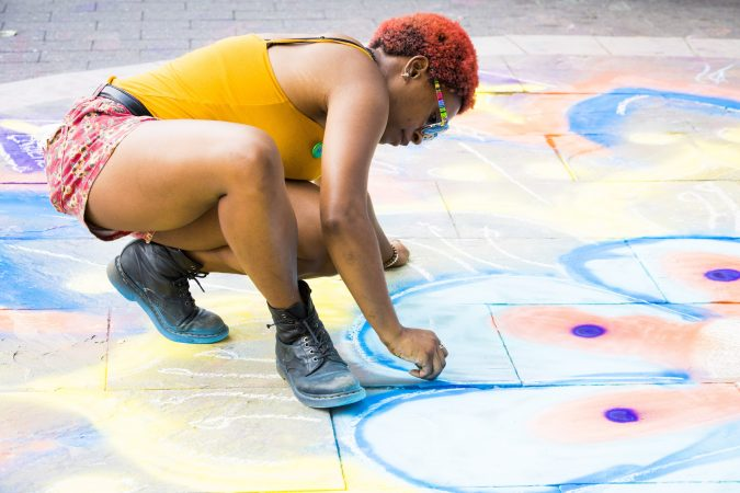 Alaina Ewins adds to a chalk mandela at the corner of Ridge Avenue and Broad Street on August 11, 2018. The mandela was created by the Mural Arts Program in support of Philly Free Streets. (Rachel Wisniewski for WHYY)