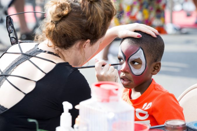 Chrissy Jones (left) paints the face of Kadeem Gaines, 3, as Spiderman at a booth advertising The Met Philadelphia at Broad and Poplar Streets on August 11, 2018. (Rachel Wisniewski for WHYY)