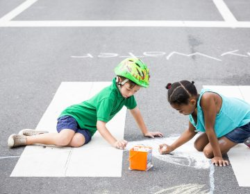 Geffen Reinherz, 5 (left), and Skyla Car, 7, draw with chalk at Broad and Poplar Streets while Broad Street is closed off for Philly Free Streets on August 11, 2018. (Rachel Wisniewski for WHYY)