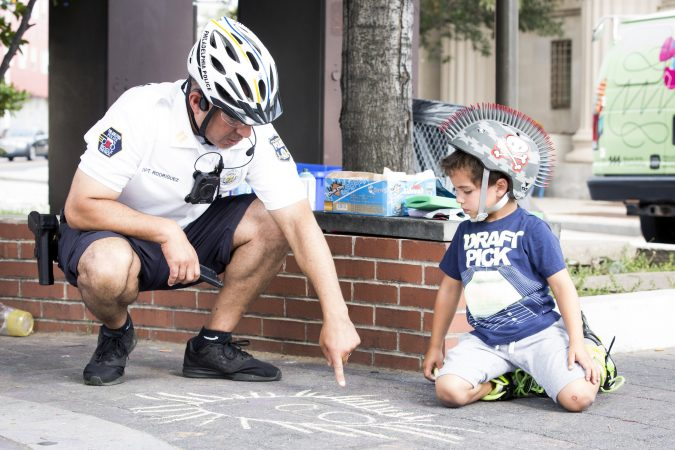 Philadelphia Police Captain Javier Rodriguez compliments Logan Miller, 5, on a monster he has drawn with chalk at Broad Street and Ridge Avenue on August 11, 2018. (Rachel Wisniewski for WHYY)