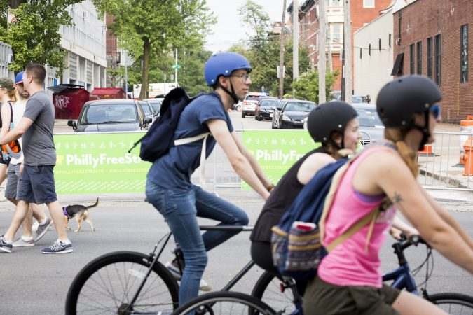 People on bikes and on foot pass in front of barriers that are blocking Broad Street from traffic as a part of the third annual Philly Free Streets event on August 11, 2018. (Rachel Wisniewski for WHYY)