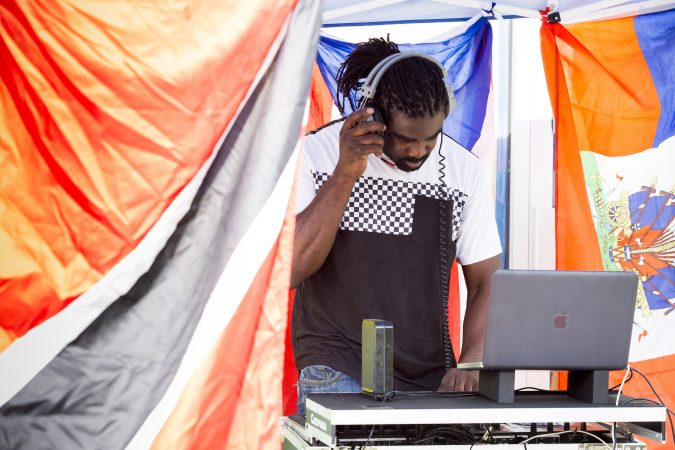 Roy Nurse DJs outside of Flambo Carribean Restaurant to draw customers in from Philly Free Streets on August 11, 2018. (Rachel Wisniewski for WHYY)