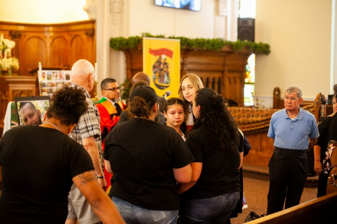 The family of Joseph Santos is comforted after a memorial service for the 44-year-old who was fatally shot on July 28, 2018 by South Whitehall Township Police Officer Jonathan Roselle. (Brad Larrison for WHYY)