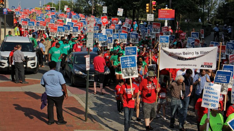 Thousands of union members march silently down Chestnut Street Wednesday in support of immigrant families. (Emma Lee/WHYY)