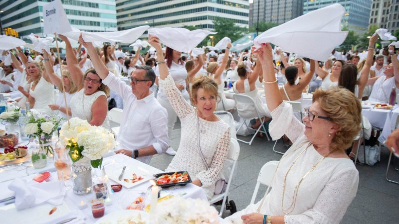 Claire Danderea (center) and Janice Bartle wave their napkins along with other diners signaling their table settings are complete. (Jonathan Wilson for WHYY)