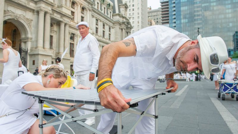 Jarrad Bradt and Taylor Morgis assemble a table at Dilworth Park.(Jonathan Wilson for WHYY)