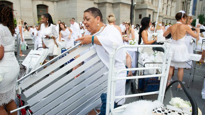As Diner en Blanc gets underway, Marcia Hinton assembles her table.  (Jonathan Wilson for WHYY)