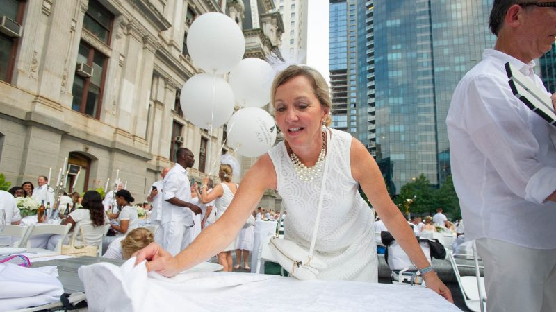 Johnine Meehan spreads a tablecloth at the start of Le Dîner en Blanc. (Jonathan Wilson for WHYY)