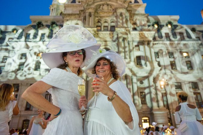 Zarbeth Teelucksingh (right) and a friend show off their hats at Le Dîner en Blanc. (Jonathan Wilson for WHYY)