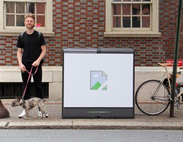 Artist Brendan Lowry stands beside his contribution to the Trashcan Takeover project at 17th and Locust streets.