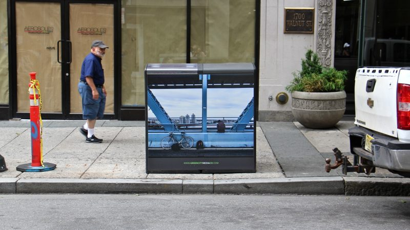 A photo by Conrad Benner adorns a trashcan at 17th Walnut streets. (Emma Lee/WHYY)