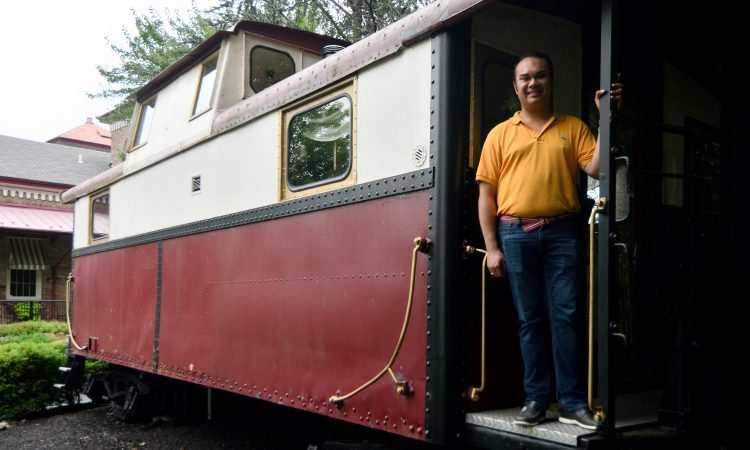 Mayor Peter Ursucheler stands on the back of a stationary caboose, located at the former train station in Phoenixville, PA, on august 21, 2018. The Colombia Station currently houses an event venue. (Bastiaan Slabbers for WHYY)