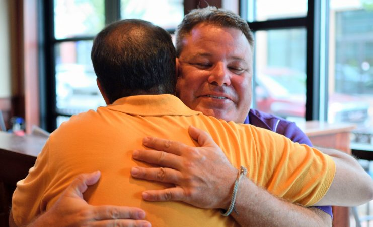 Mayor Peter Ursucheler and developer Manny DeMutis embrace upon meeting at Iron Hill Brewery in Phoenixville, PA, on August 21, 2018. (Bastiaan Slabbers for WHYY)