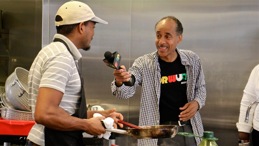 WURD Radio's Mike Thomas interviews chef Chris Paul during a cooking demonstration at Founder's Day, celebrating the legacy of WURD founder Walter P. Lomax, Jr.