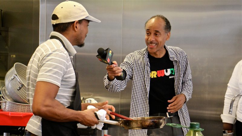 WURD Radio's Mike Thomas interviews chef Chris Paul during a cooking demonstration at Founder's Day, celebrating the legacy of Walter P. Lomax Jr. (Emma Lee/WHYY)