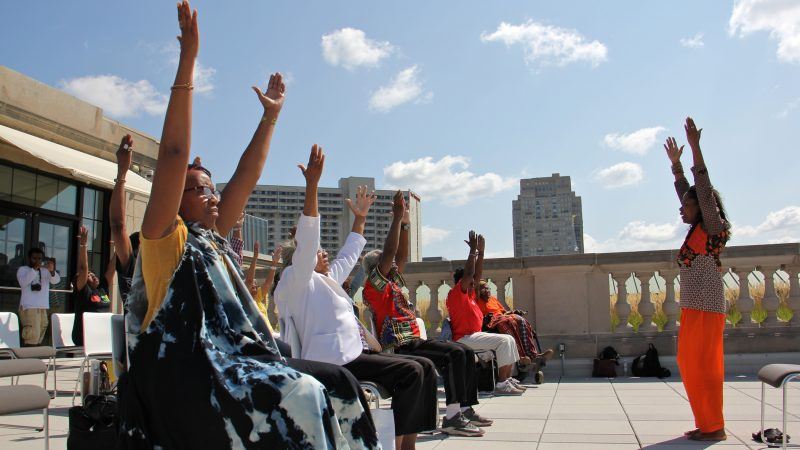 Dr. Robbin Alston leads a seated yoga class on the Terrace of the Free Public Library during Founder's Day, celebrating WURD Radio founder Walter P. Lomax Jr. (Emma Lee/WHYY)