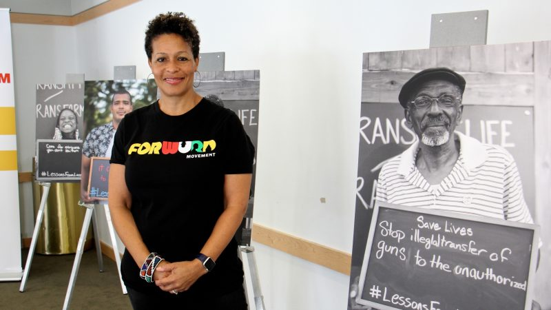 Sara Lomax-Reese, president and CEO of WURD Radio, presides over Founder's Day, which celebrates the legacy of her father, Philadelphia physician and entrepreneur Walter P. Lomax, Jr., who founded the radio station. She stands among posters created for WURD's Transmit/Transform multimedia project aimed at stopping violence. (Emma Lee/WHYY)