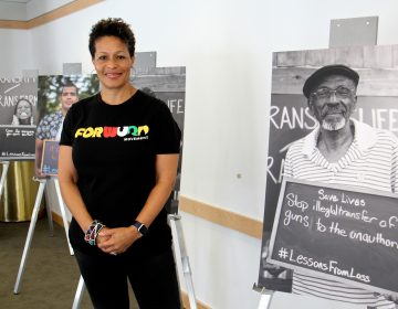 Sara Lomax-Reese, president and CEO of WURD Radio, presides over Founder's Day, which celebrates the legacy of her father, Philadelphia physician and entrepreneur Walter P. Lomax, Jr., who founded the radio station. She stands among posters created for WURD's Transmit/Transform multimedia project aimed at stopping violence.