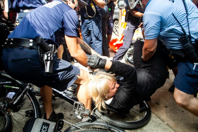A protestor is brougt down by Philadelphia Police during a scuffle that broke out on Race Street between Antifa protestors and the police. (Brad Larrison for WHYY)